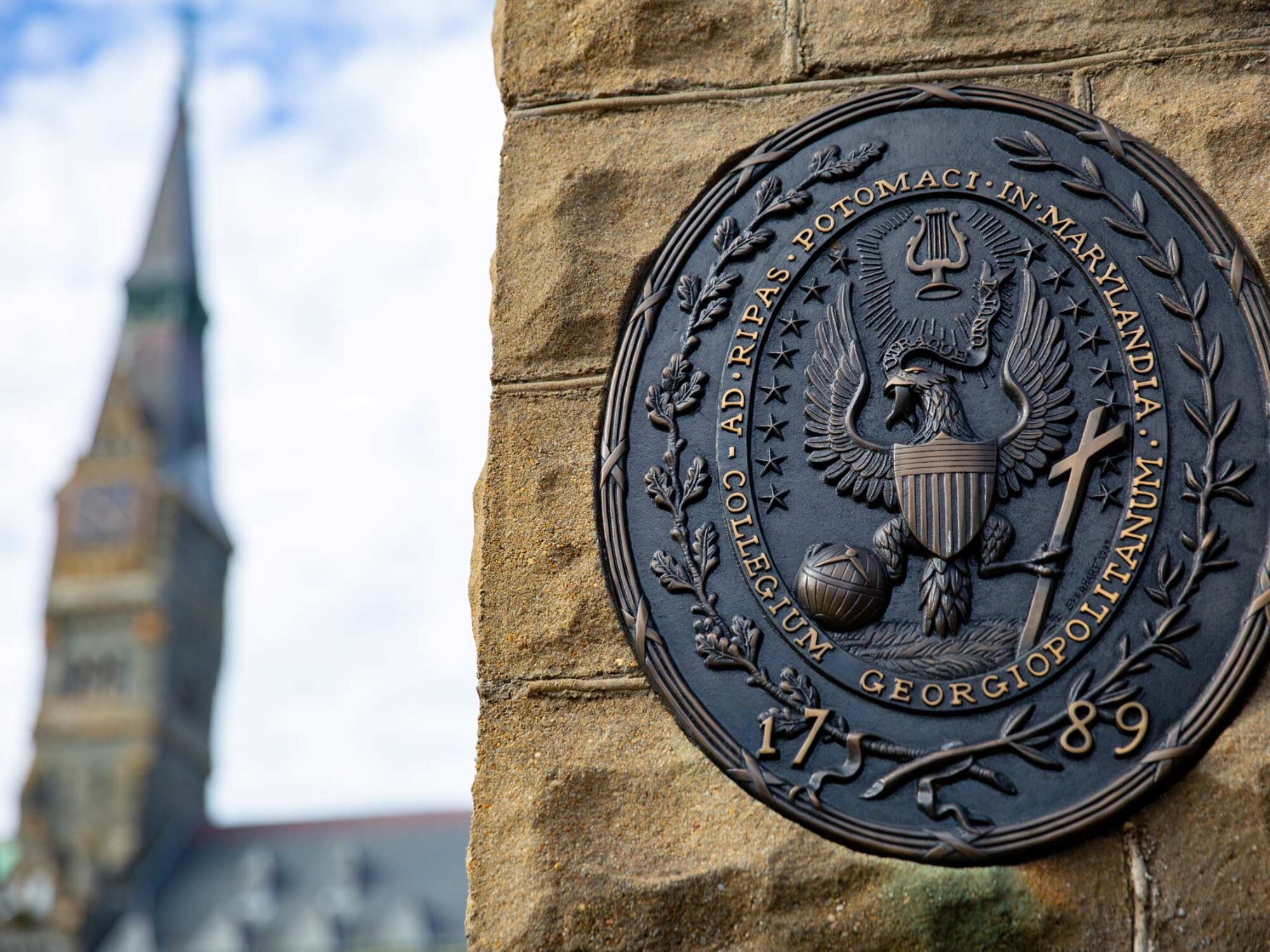 The Georgetown Seal at the gates of the university's main campus with Healy Hall's spire in the background