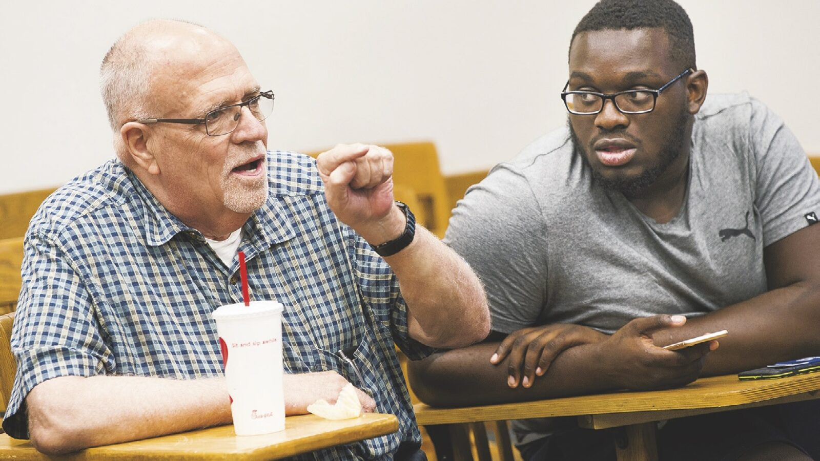 Father Raymond Kemp (left) leads a discussion with students during the Cura Personalis seminar.