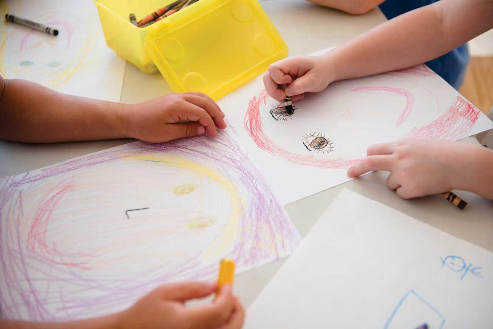 Students drawing with crayons