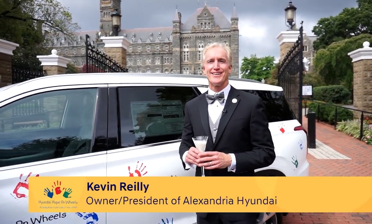 Kevin Reilly in a tuxedo with a champagne flute of Milk at the Healy Gates