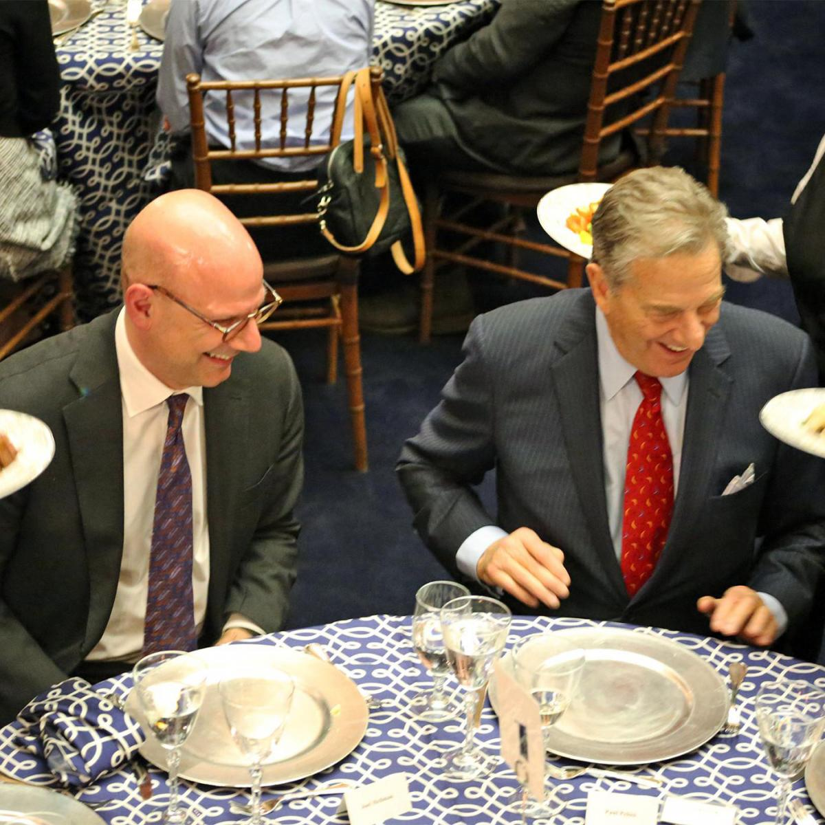 Joel Hellman and Paul Pelosi seated at a table during the scholars program at the SFS Board of Advisors Dinner in Riggs Library