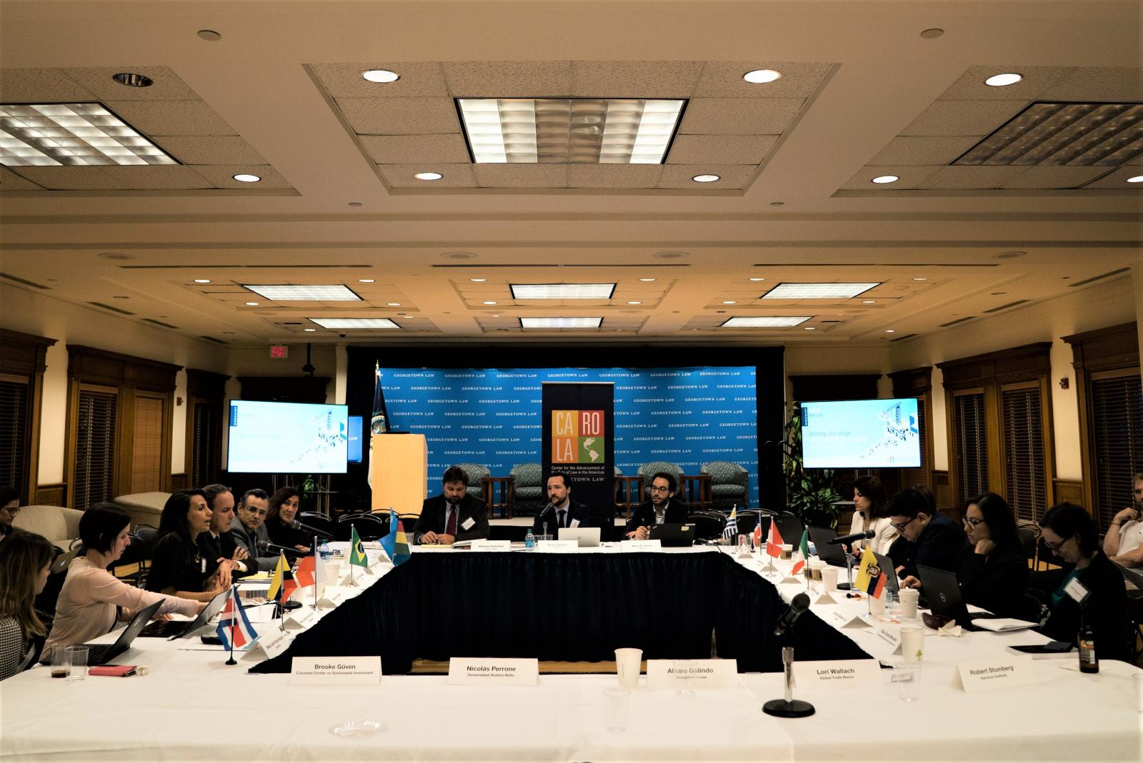 Representatives of Latin American governments, universities, and NGOs talk around a large square table in a room at the Georgetown Law Center. Name tags, country flags, and microphones are set out on the tabletop in front of the representatives.