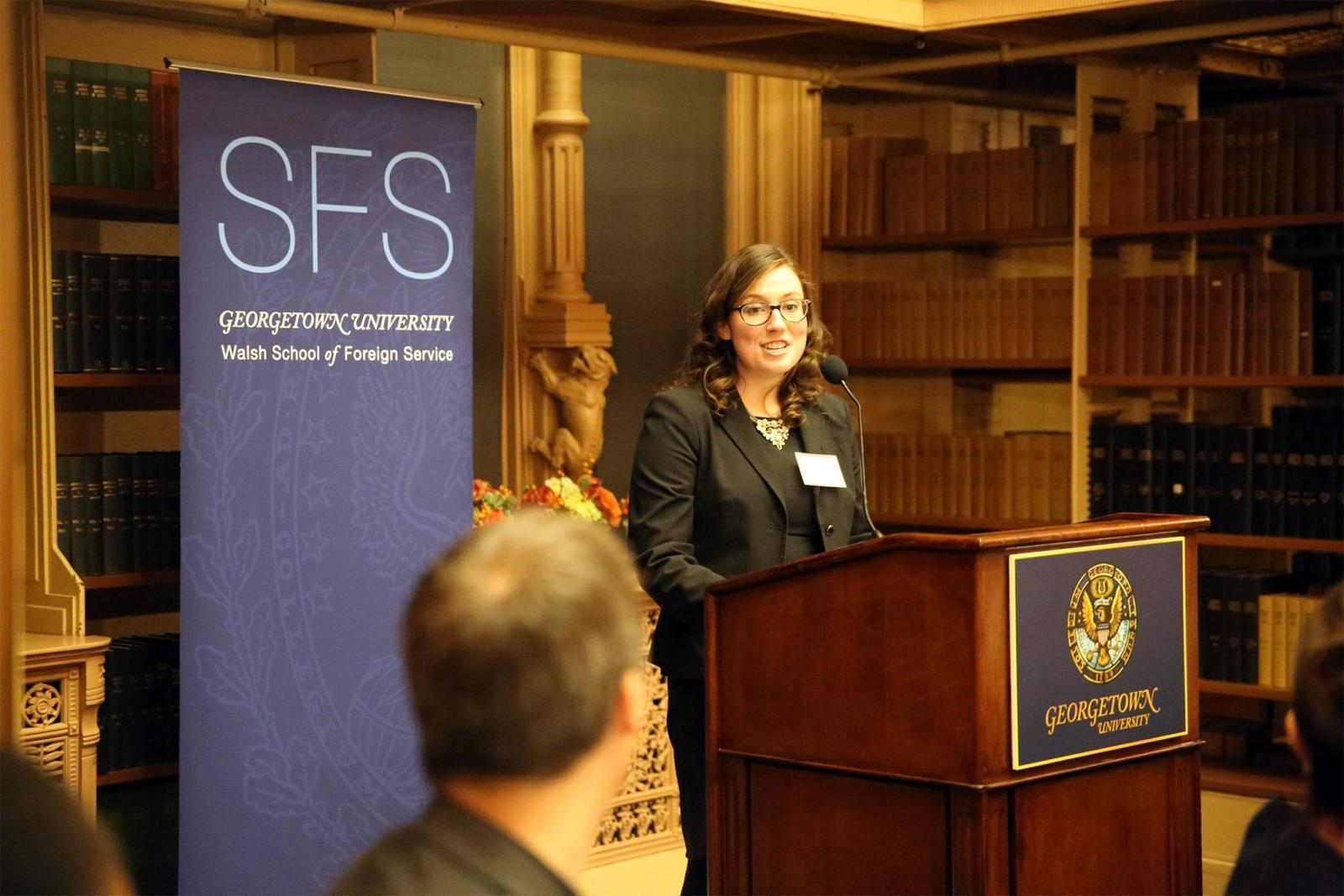 Megan Murday standing at a podium in Riggs Library addressing the SFS Board of Advisors Dinner