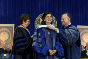 NHS Dean Patricia Cloonan and President John J. DeGioia present Luci Baines Johnson with an honorary Georgetown University academic hood in 2018.